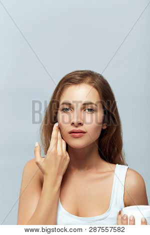 Beauty Concept. Woman Holds A Moisturizer In Her Hand And Spreads It On Her Face  To Moisturize Her