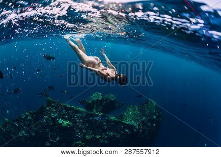 Woman Freediver In Bikini Swin In Tropical Ocean At Shipwreck