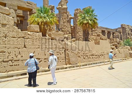 Karnak, Egypt - 17th May, 2018: Two Adult Caucasian Tourists Visiting The Interior Of The Temple Of