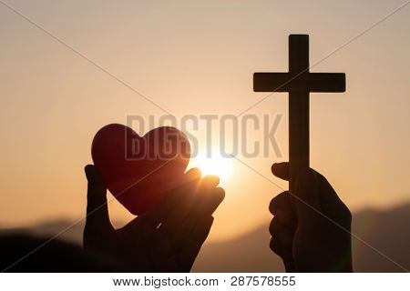 Silhouette Of Woman Hands Praying With Cross And Holding A Red Heart Ball  In Nature Sunrise Backgro