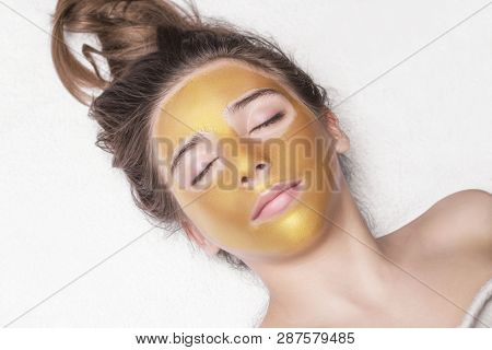 Beautiful Girl With A Cosmetic Mask On The Face Of Golden Color. Beautiful Model Removing Golden Fac