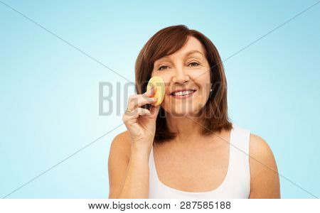 beauty, skin care and old people concept - smiling senior woman cleaning her face with exfoliating sponge over blue background poster