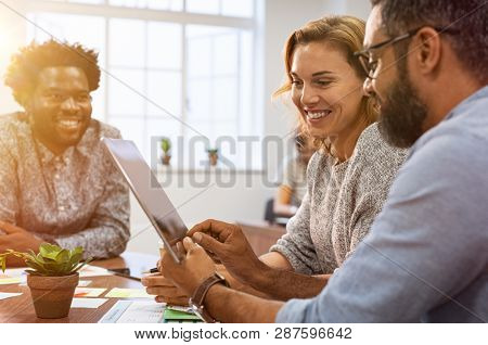Successful business people discussing while using digital tablet in office. Multiethnic business team working on tablet in their company. Mature businessman showing data on screen to smiling woman.