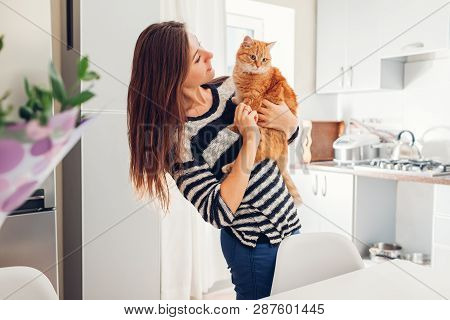 Young Woman Playing With Cat In Kitchen At Home. Girl Holding And Hugging Ginger Cat