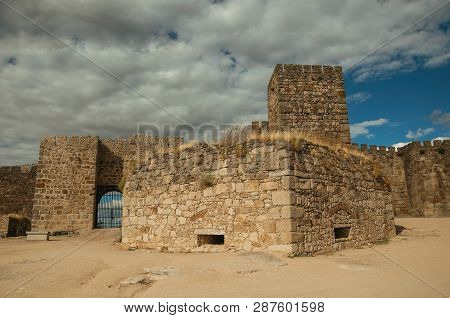Towers And Stone Walls Facade With Merlons, In A Cloudy Day At The Castle, Also Called Alcazaba, Of