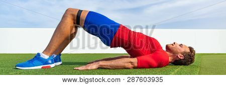 Exercise fitness man training body with resistance band core workout bodyweight exercises doing butt lift bridge glutes activation banner panorama.
