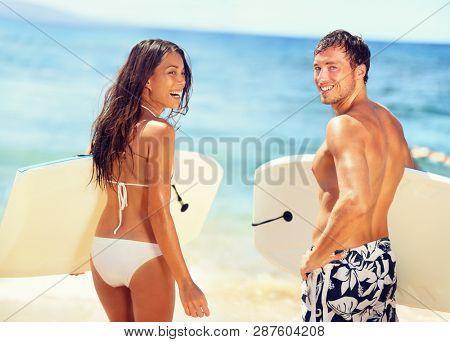 Surfers on beach having fun in summer. Surfer woman and man with boogieboard smiling happy on beach on Hawaii. Multiracial couple Asian woman and Caucasian man in outdoor water activity during travel