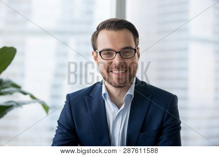Businessman In Suit Looking At Camera Making Conference Video Call