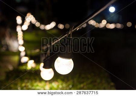 Outdoor String Light Bokeh Background. Light Bulb Hanging On A Line In Backyard. Blurry Lights Decor