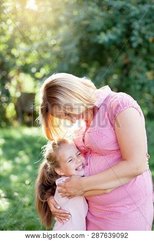 Pregnant Young Woman And Child Girl Are Happy, Smilng And Hugging In Sunset Garden. Mother And Daugh