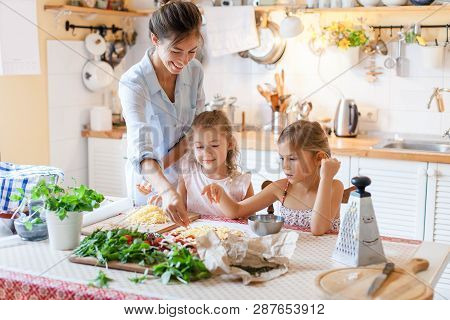 Family Are Cooking Italian Pizza Together In Cozy Home Kitchen. Cute Kids With Happy Mother Are Prep