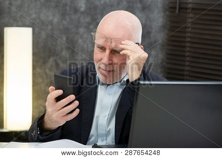 A Senior Businessman Using  Smartphone, He Is Having Difficulties And Vision Problems