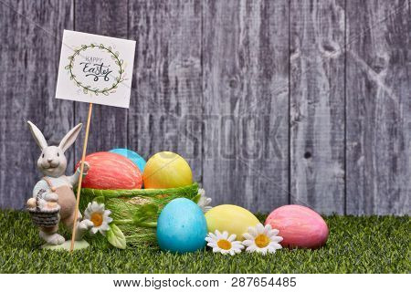 Colored easter eggs, easter rabbit and flowers lying on a green grass on a grey wooden  background with copy space. Greeting card, Easter background