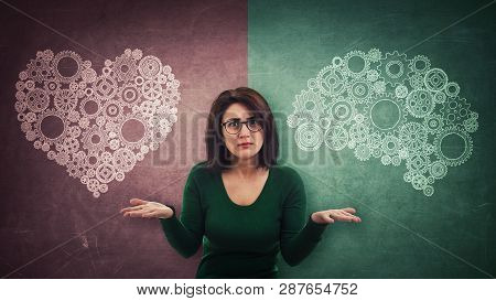 Perplexed Woman Over Split Blackboard With Heart And Brain Symbol On Different Sides. Difficult Deci