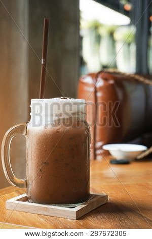 Iced Cocoa In Glass Jar On The Wooden Table.