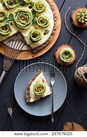 Raw Vegan Dessert. Homemade Pie With Kiwi Roses, Berries And Cream Filling On Nutty Crust On Dark Ba
