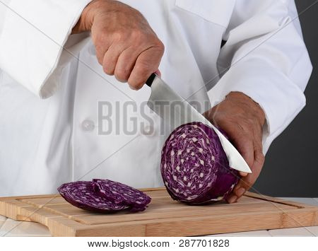 Closeup of a chef cutting a head of red cabbage on a wood cutting board. Horizontal format on a light ot dark gray background. Man is unrecognizable. Model Rleased.