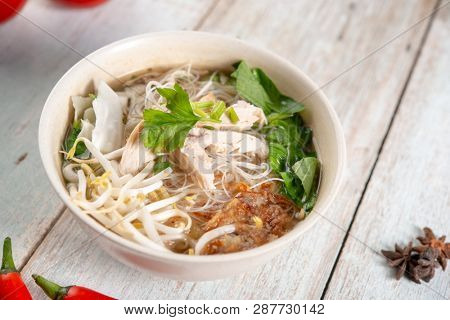 Asian rice noodles soup with vegetables and chicken in bowl on wooden background.