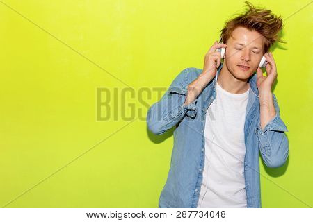Attractive Handsome Young Guy Listening Music By Using Headphone. Cool Guy Gets Happy And Relaxed. C