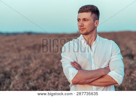 A Young Man In A White Shirt, In The Summer On Wheat Field, Looks Into The Distance. Free Space For