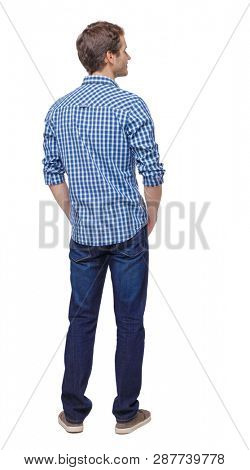 Back view of man in dark jeans. Standing young guy. Rear view people collection.  backside view of person.  Isolated over white. The guy in sneakers and shirt stands with his hands in his pockets.