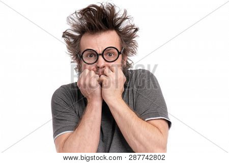 Crazy Scared Man with funny Haircut in eye Glasses, bites his nails and looks worried. Bearded guy afraid and shocked, isolated on white background. Emotions and signs concept.