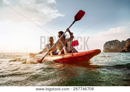 Happy Couple Walks By Sea Kayak Or Canoe At Tropical Bay