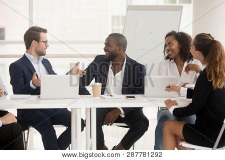 Multiracial Employees Sitting At Boardroom Desk Listening Team Leader