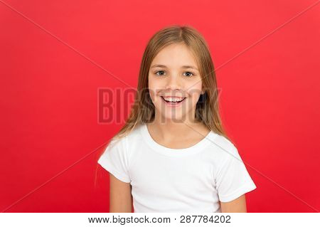 Smiling Beauty. Brilliant Smile Concept. Girl Happy Smiling Face Over Red Background. Emotional Kid
