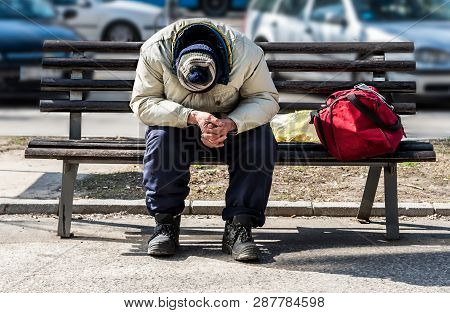 Homeless Man, Old Poor Homeless Man Or Refugee Sleeping On The Wooden Bench On The Urban Street In T