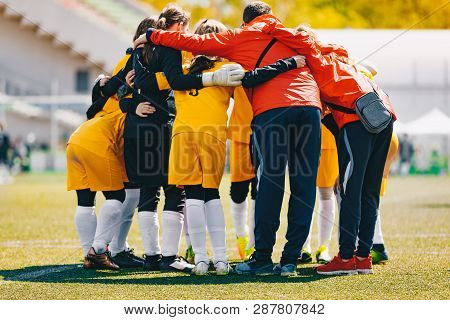 Coach Coaching Girls Sports Team. Girls School Sports Team Huddling With Coach On The Grass Field. S