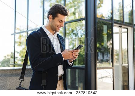 Handsome young business man wearing suit walking outdoors, using mobile phone, carrying bag