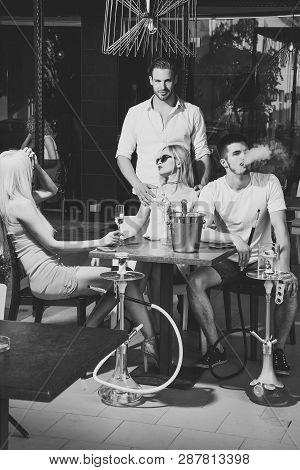 Twins Women And Men Friends Relax In Cafe Outdoor. Man Vapor Hookah Pipe In Shisha Bar Lounge. Addic