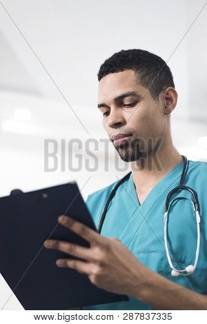 Men In A Cyan Colored Dental Coat Taking Notes