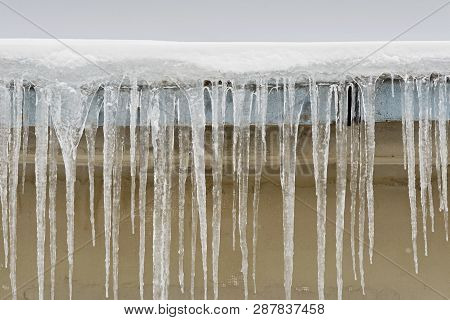 Big Icicles Hang From The Roof Of A House