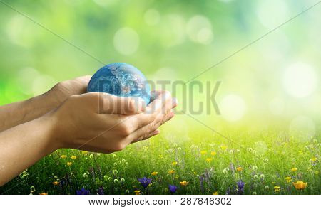 Earth day holiday concept.Close up image of human hands holding  planet earth against green nature background.Environment  concept. 
