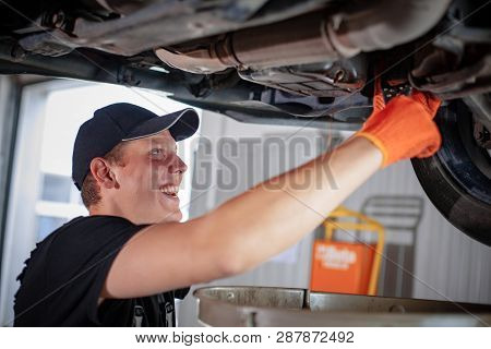 Specialist Auto Mechanic In The Car Service Repairs A Car.