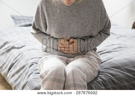 Sick Woman In Grey Homewear Sitting On Bed, Keeping Hands On Stomach, Suffering From Intense Pain. I