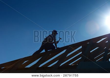 Carpenter Or Joiner Working On Top Of The Roof