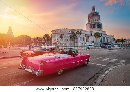 HAVANA,CUBA - MARCH 3,2019 : Classic cars and the Capitol building in downtown Havana at sunset
