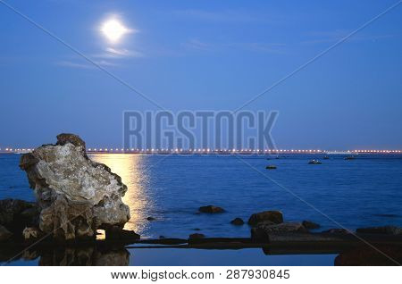 Night Shore Of The Bay In The Moonlight And The Lights Of The Dam In The Background