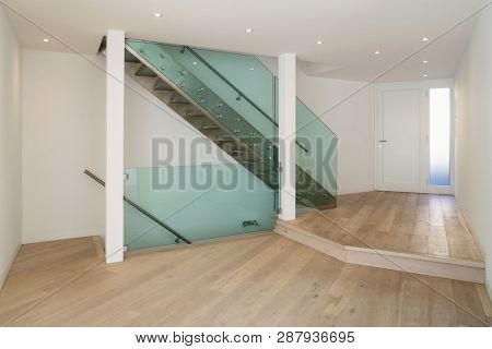 Entrance detail with modern glass staircase and parquet. Spotlights. Nobody inside