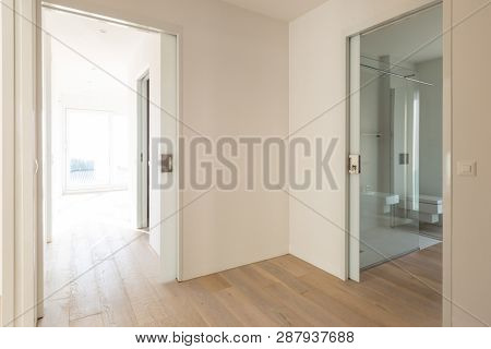 Corridor with open room doors and modern bathroom. Nobody inside and white walls.