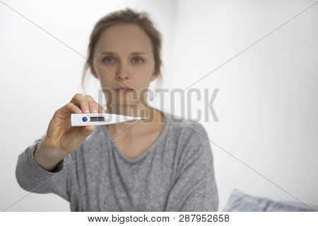Sick Young Caucasian Woman In Grey Sweater Sitting On Bed, Showing Thermometre, Looking At Camera. T