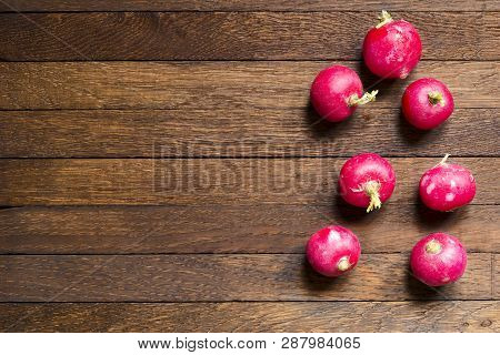 Red, Raw, Whole Radishes On Dark Brown Wooden Table. Copy Space. Objects In Right Position. Close Up