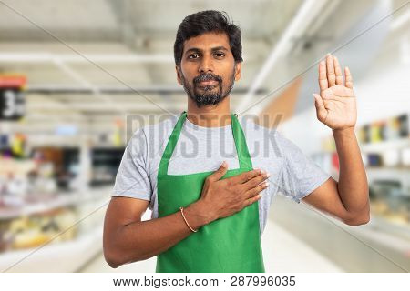 Serious Trustworthy Indian Male Hypermarket Or Supermarket Employee Making Honest Oath Gesture With