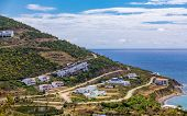 Rows of Modern Coastal Condos along roads on a terraced hill overlooking the sea poster