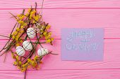 Spring Easter festive background. Easter nest with styrofoam festive eggs and pussy willow twigs on a wooden background with a congratulatory inscription. poster
