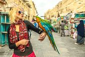 Happy woman kisses a parrot at Bird Souq inside Souq Waqif, the old market and tourist attraction in Al Souq District, Doha city center, Qatar. Caucasian traveler visits Middle East, Arabian Peninsula poster