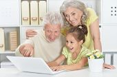 Portrait of grandparents with granddaughter using tablet poster